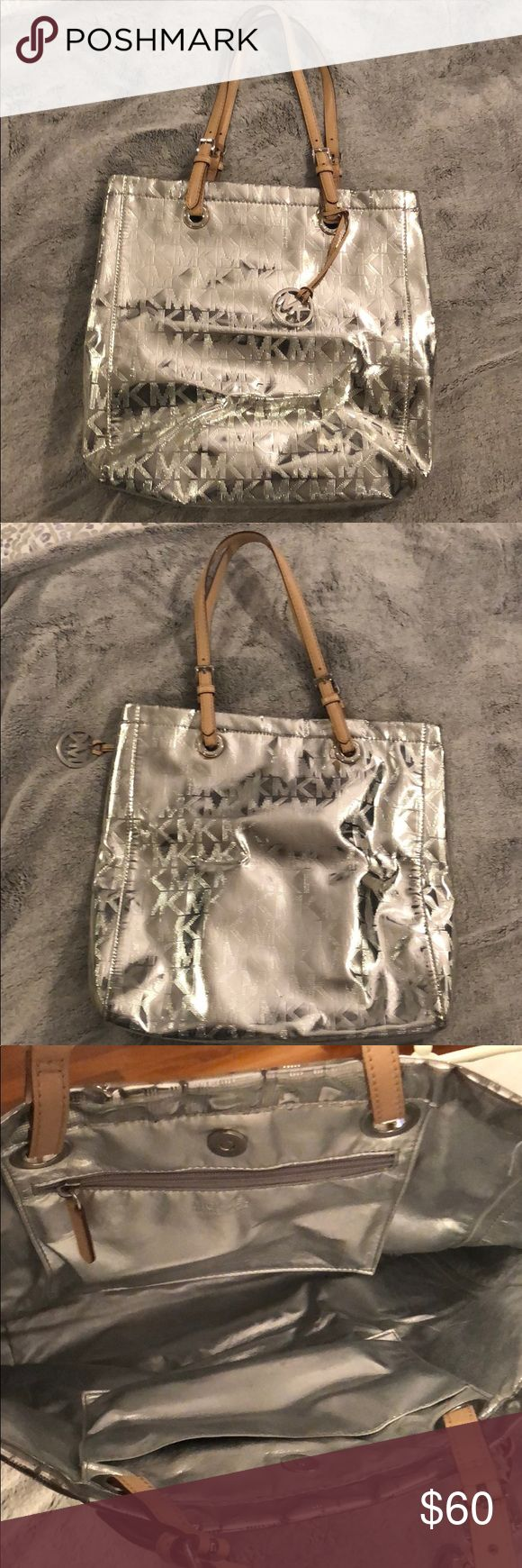 Michael Kors Silver Tote Bag Silver MK Michael Kors tote bag. MK key chain hanging from the handle. This tote bag is like new with barely any signs of wear. Minimally worn and in great condition KORS Michael Kors Bags Totes