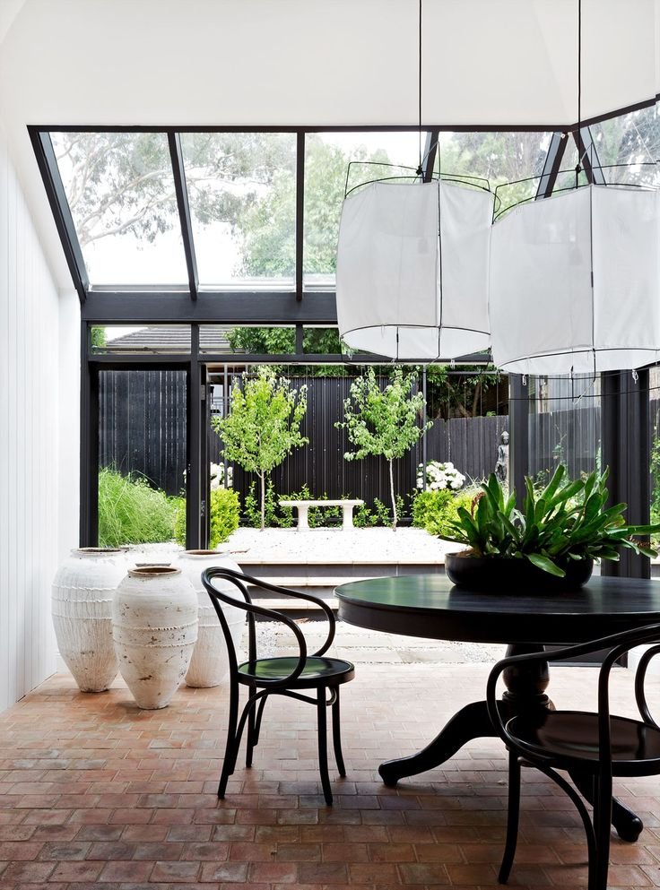 Atrium/sunroom overlooking garden: black window frames, black Thonet bentwood chairs, black round wooden dining table, white fabric lampshade pendant lights, large white urns, brick pavers, black fence