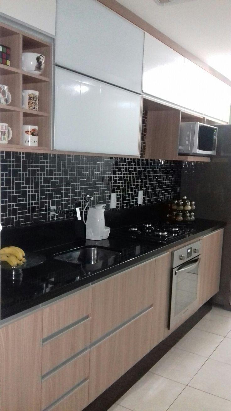 Cozinha com armários em tons de branco e madeira. Pia em granito são gabriel e pastilha geométrica preta com rejunte branco.