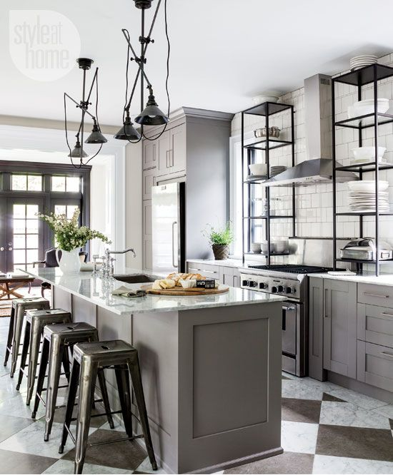 A grey on grey kitchen with black and chrome accents deliver warmth and depth across this Victorian house.