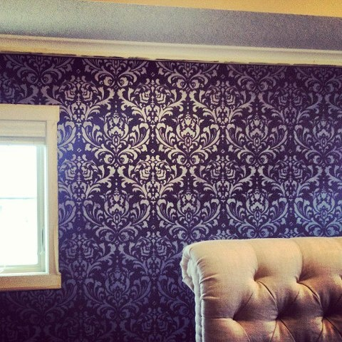 stenciled purple accent wall with decadent gold furnishings
