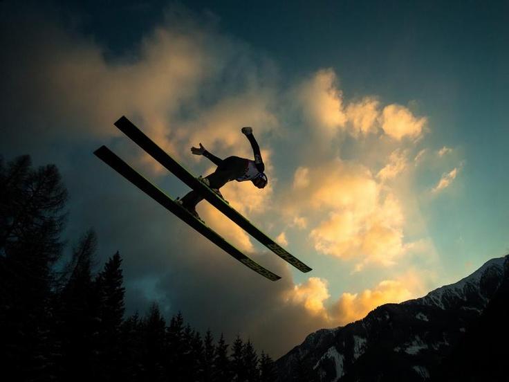 Trainingsidyll: Der Österreicher Gregor Schlierenzauer springt im Abendlicht beim Training von der Schanze im italienischen Predazzo. (Foto: Jürgen Feichter/dpa)