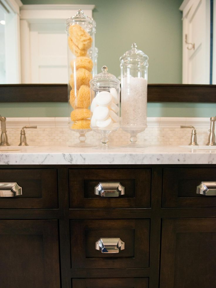 Three glass containers are set upon this gorgeous marble and dark wood double vanity to display bath salts and soaps.