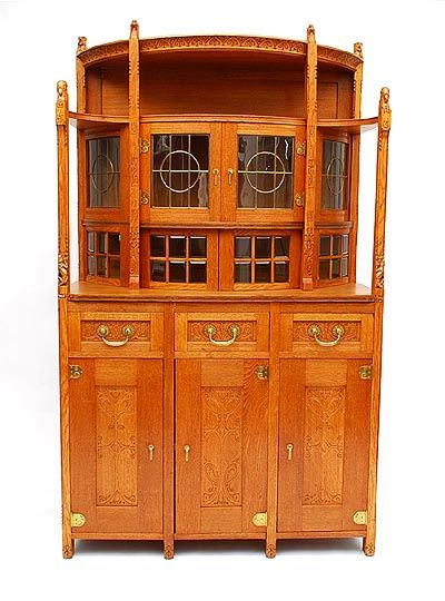 Oak Nieuwe Kunst cabinet with three doors below three drawers the upper part with a semi-circular vitrine cabinet the vertical supports carved with lizards leading to cockatoo's heads the four vitrine's supports with cockerel's heads terminals further carved with stylised floral patterns designer execution unknown the Netherlands ca.1900