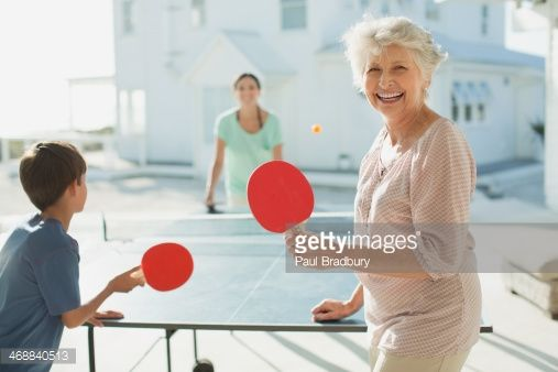 Stock Photo : Multi-generation family playing table tennis outside beach house