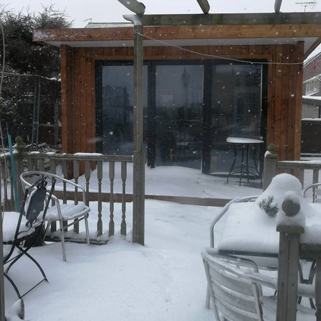 There is a snow drift outside the garden office.