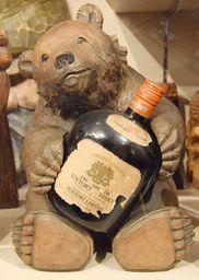 ウイスキーボトルを抱く木彫りの熊 民芸にみる民族文化〜ウイスキーボトルを抱く木彫りの熊。老舗のスナックやバーなどで今も見かけることがある。一升瓶を抱く木彫り熊もある