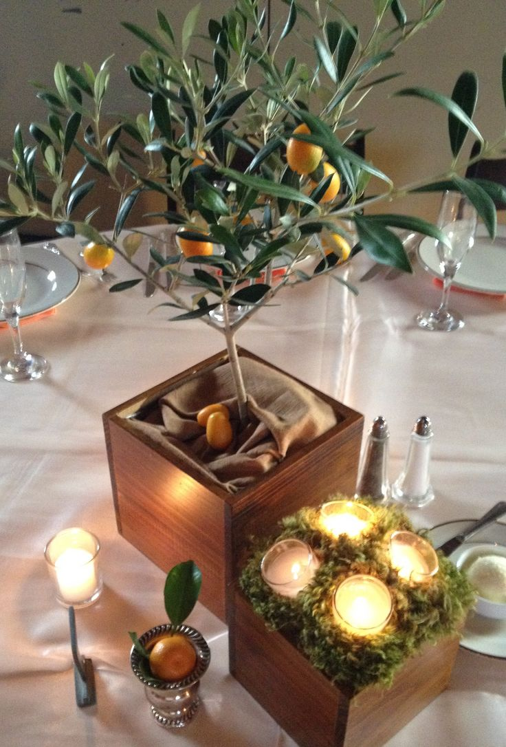 table arrangement at citrus wedding reception is a small citrus tree placed in a varnished wood box and topped with burlap. it is accented with a smaller wood box topped with fresh clump moss and votives