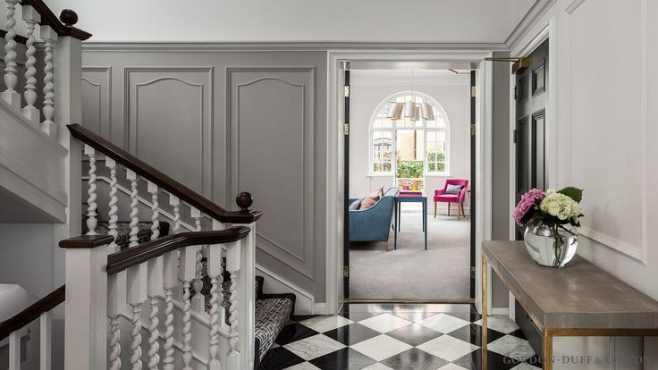 Entrance hall in period property on Sloane Street. Black and white checker-board floor tiles. Panelling and mouldings on walls. Shagreen console table.