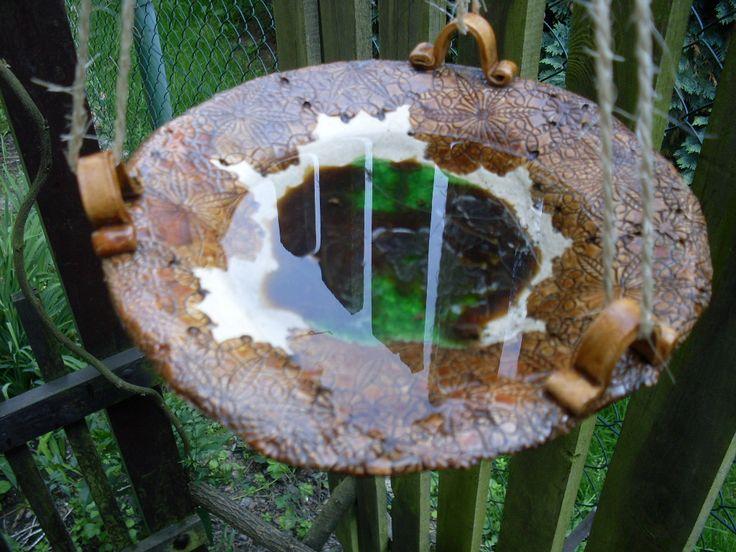 Pítko pro ptáky Pítko nebo krmítko pro ptáčky ve tvaru talíře má průměr 25 cm. Je třeba ho zavěsit na lanko nebo drátek. Je naglazováno rezavou glazurou a na dně má roztavené zelené a hnědé sklo.