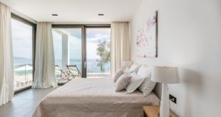 GREEK STYLE VILLAS - Bedroom with white linens and large windows with sea views.