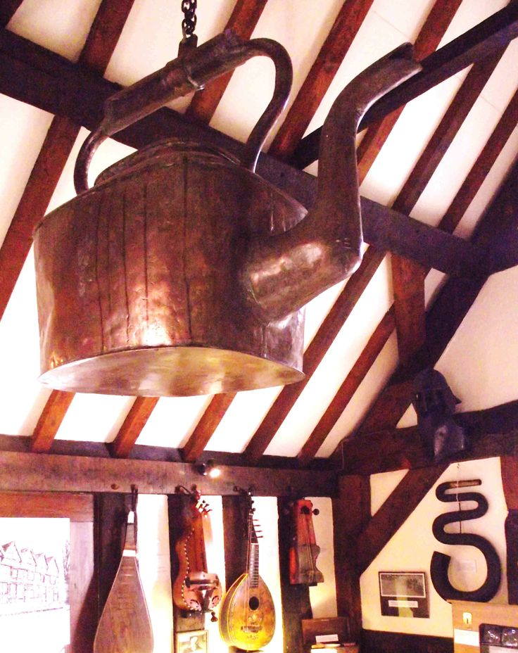 A large copper kettle used to hang in Ledbury's High Street. Now it's in the Butcher Row House, Church Lane - a tiny museum crammed with strange old things. Notice the 'serpent', a wind instrument, on the back wall.  [Philip Weaver]