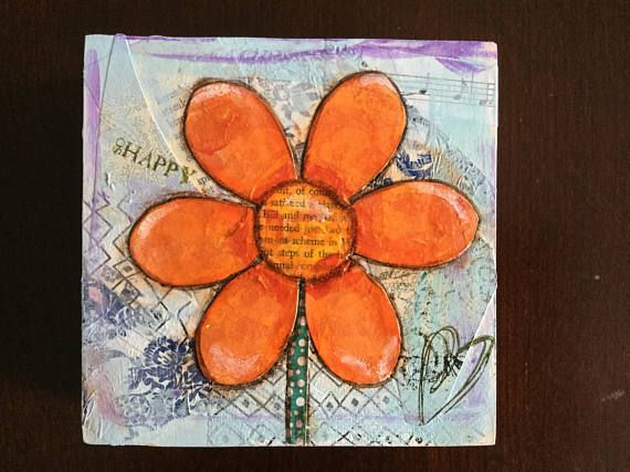 This fun orange flower is mixed media created on a square piece of wood. The process begins by adding layers of paper, sheet music and book pages to the wood to create a wonderful texture. I then add paint over top of the paper. The flower itself is made from layers of tissue paper and a touch of paint. Its outlined in ink. The finishing touch is to add stamps. The wood is 5 x 5 and 2 deep. The sides are painted and finished too. It is sealed for protection and signed by me on the back. Pr...