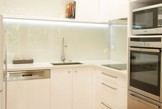 Glass splashback in kitchen renovation with LED strip lighting