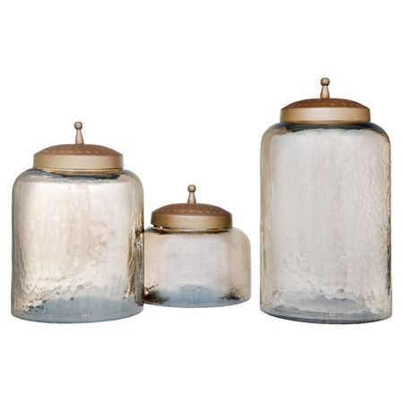 Add a charming touch to your kitchen counter or entryway console table with these lovely canisters, crafted of glass and showcasing hammered details.