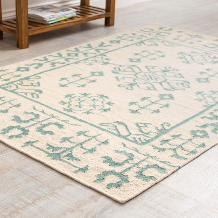 Shanti Kilim Rug this flat weave kilim rug woven with traditional stylised floral patterns in teal on cream.