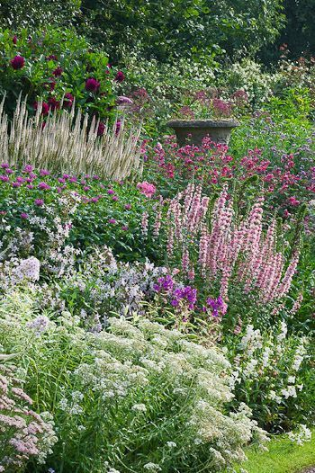 Delicate blooms in pink, white, and purple nearly cover the antique urn in this English garden at Wollerton Old Hall. Photo by Clive Nichols Garden Photography.