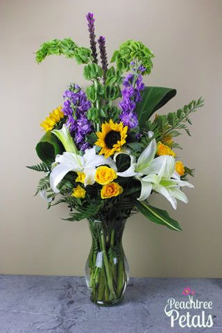 The White Diamonds Bouquet is a very simple yet elegant arrangement of bells of Ireland, lavender stock, yellow spray roses, sunflowers and fragrant white oriental lilies. Our designers custom design