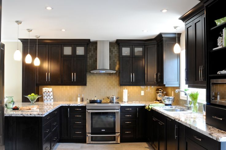 """The wall between the kitchen and dining room was removed to open up this space for a busy family and allow better access to their backyard pool by getting rid of the """"kitchen""""table. Visit me on Houzz or www.carolinemckaydesign.com.  #oakville #interiordesign #oakville renovation #blackkitchen #glasstilebacksplash"""