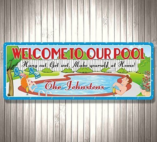 Welcome To Our Pool, Hang Out, Get Wet Personalized Sign with Couple, Swimming Pool Decor. Invite everyone to hang out and get wet with this personalized pool sign! Relaxing blue water and a lounging couple take center stage in a cozy background scene with trees, bushes, potted plants and a white fence. Hair color may be changed, as well as any text. Add to your home decor collection or give as a unique personalized gift! • Printed on Durable Vinyl • Mounted on 1/2'' Weatherproof PVC • UV...