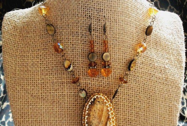 Polodrahokam pieskový jaspis je obšitý najkvalitnejším japonským rokajlom značky toho v zlatom a béžovom odtieni.  Zavesený je na retiazke pozostávajúcej z rôznych tvarov tlačeného, perleťe a veľkých brúsených ohňoviek.  Náušničky sú zhotovené z rovnakého materiálu.  Možnosť zakúpiť aj osobitne !