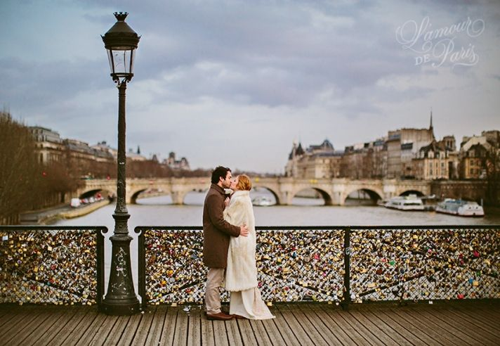 A couple locking their padlocks onto the Pont Des Arts bridge in Paris in a romantic tradition to celebrate their love. OBSESSED with this photo by Stacy Reeves.
