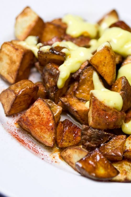 Recipe for Catalan style Patatas Bravas with Allioli (aioli). Patatas Bavas are crisp potatoes fried in duck fat with a spicy pepper sauce and creamy garlic allioli.