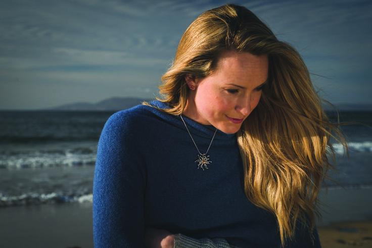Leonie Cornelius models a handmade hallmarked gold and silver Nebula pendant by Martina Hamilton during a photo shoot on Edenreagh Strand in North Sligo