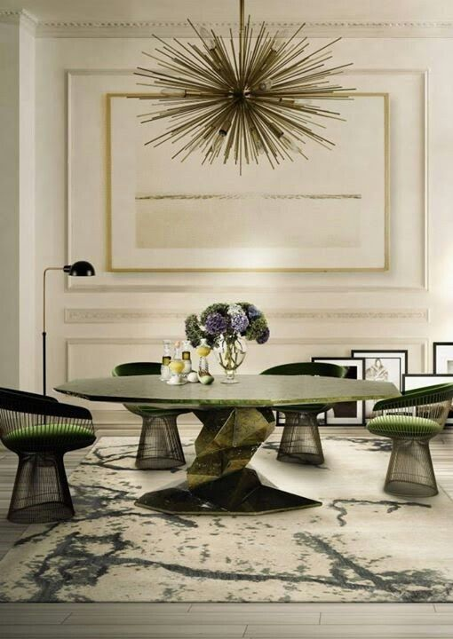 Eclectic dining area: Platner chairs, a sputnik chandelier, abstract table, and painterly rug in a modern room.
