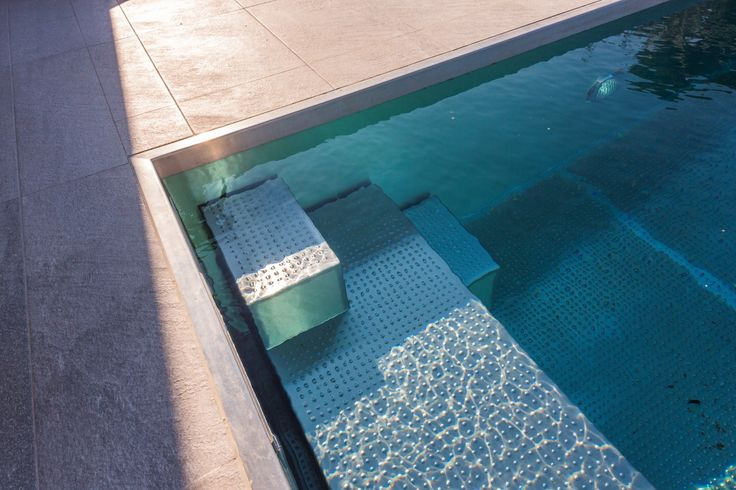 Detail od stainless steel pool stairs with resting area
