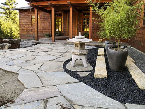Japanese Style courtyard with flagstones, black pebbles, statue and bamboo in pots