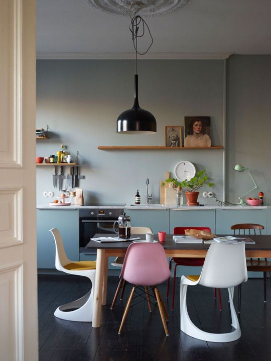 Pale baby blue kitchen and colorful vintage chairs
