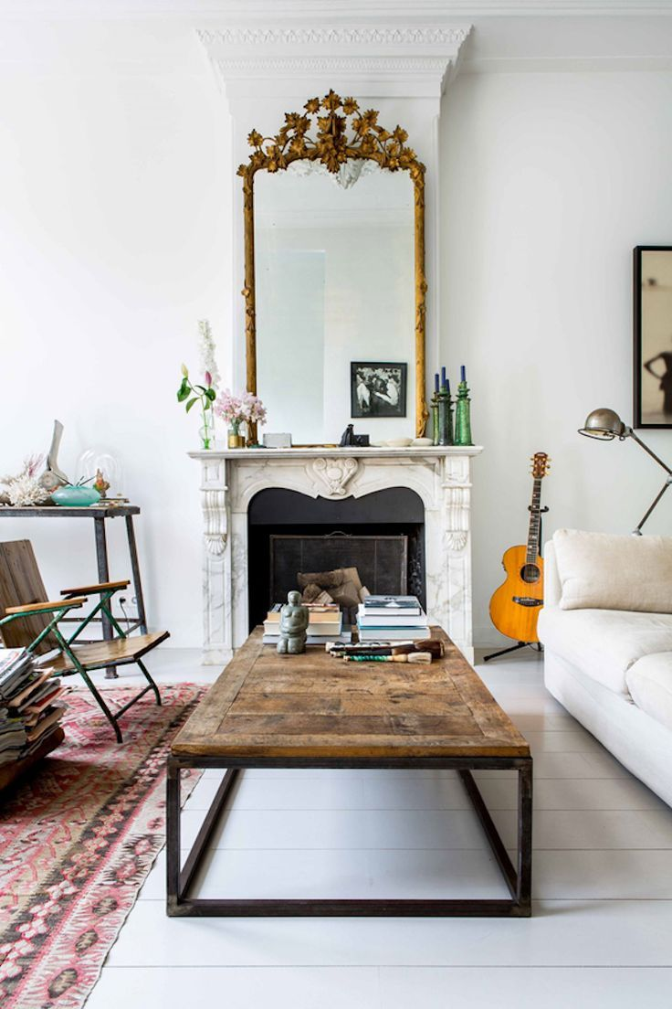 Living room with a mix of vintage ornate elements, such as a Victorian mirror and fireplace, and modern elements like a mid-century coffee table