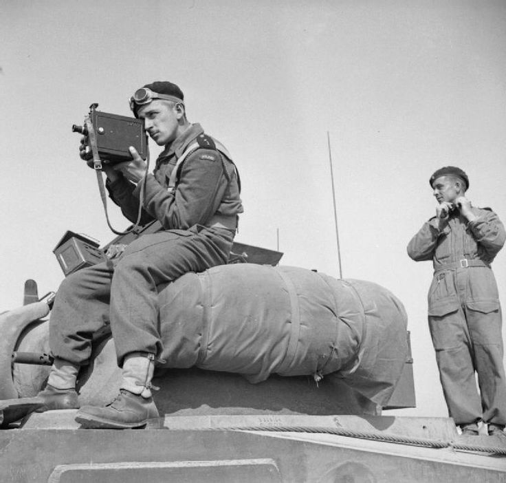 2nd Lieutenant Jerzy Januszajtis, a Polish Army Film Unit cameraman, films from the top of a Sherman tank of the 1st Polish Armoured Division tank during Operation 'Totalise', south of Caen, Normandy on 8 August 1944. He is using a De Vry camera fitted with a sling. 1944-08-08