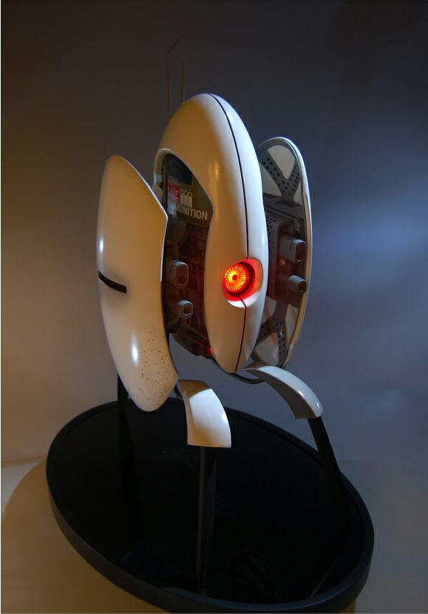 """""""Defend Your Home With Your Very Own Portal 2 Turret""""  Valve and the merchandise vendor, Gaming Heads, has teamed up together to bring you the latest in nerdy décor. The Aperture turret stands at approximately 16 inches tall and includes a motion sensor that activates the eye light of your deadly friend. The turret is constructed of poly-stone, and is hand painted and finished. The statue also comes packed in a foam interior full coloured box with a validation card that ensures your p"""