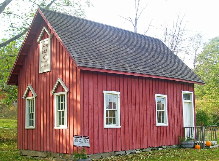 """A small red wooden house with vertical siding, a black roof, white trim and a small wooden porch near the right with two pumpkins at the bottom. Signs on the lefthand side of the building and at the bottom, on the ground, both read """"Indian Rock Schoolhouse"""""""