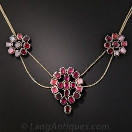 A romantic and ravishing necklace dating back to mid-nineteenth century Great Britain. Hand-fabricated in silver and 15K gold, a pair of flower blossoms and a centerpiece, connected by double fine mesh gold chains, glitter and glow with rich raspberry red, foil-backed garnets. A classic beauty.