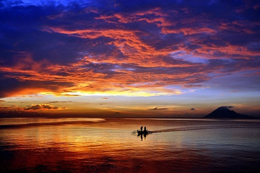 Two fishermen returning from the sea and close their boat to the beach in Manado, Sulawesi.