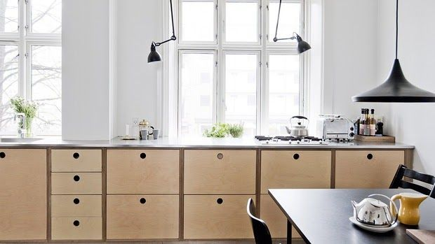 white scandinavian kitchen with black lamps, plywood drawers with fingerholes