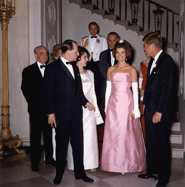 First Lady Jacqueline Kennedy, President John F. Kennedy, André Malraux, Marie-Madeleine Lioux Malraux, Lyndon B. Johnson and Lady Bird Johnson having just descended White House Grand Staircase on their way to a dinner with the French cultural minister, April 1962. The First Lady wears a gown designed by Oleg Cassini