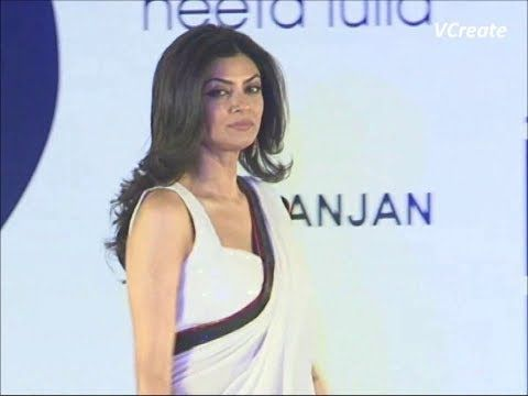 Sushmita Sen walks the ramp in a white sleeveless saree blouse.