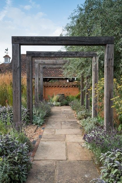 An oak pergola, weathered to an attractive silver gray, marks the entrance to the house, ushering visitors down a York stone pathway. Traditional herbs of lavender, purple sage, and bronze fennel line the beds, heralding back to the site's agricultural roots. At the end, a glazed ceramic urn provides a focal point. Photo by: Elliot Hook.