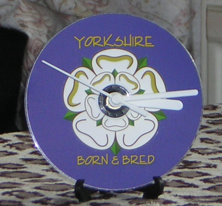 "Yorkshire CD Desk or Wall Clock. This clock is a must for anybody from England's finest county.  Printed direct to disc with a matt finish, this CD clock features the White Rose of Yorkshire on a blue background with the words ""Yorkshire - Born & Bred"" printed in yellow.  A customisable made-to-order clock with a large choice of handsets available and the additional options of a small amount of text & the inclusion of a 12-hour numeric clock dial in white."