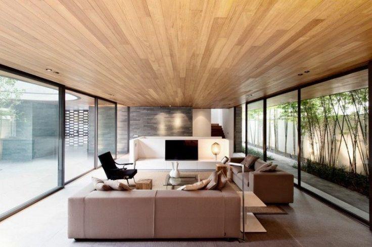 lambris bois plafond, paroi en pierre grisâtre, canapé droit blanc neige et…