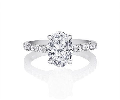 Timelessly elegant, this 1.6 mm (0.06 in.) wide platinum ring has been meticulously designed and crafted with a four-prong-set oval shape solitaire and round brilliant pavé diamonds....