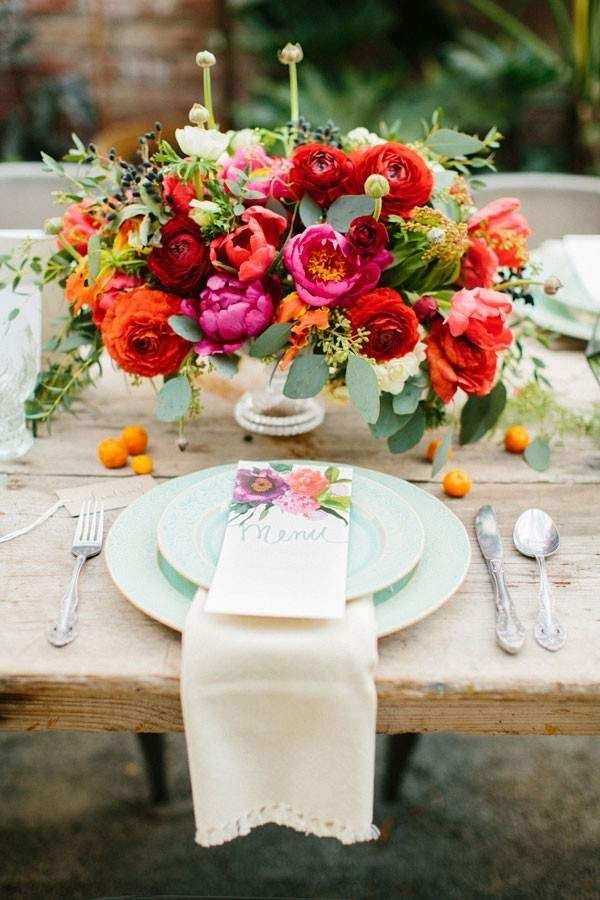 bright wedding centerpiece with peonies, ranunculus, and parrot tulips in reds and pinks