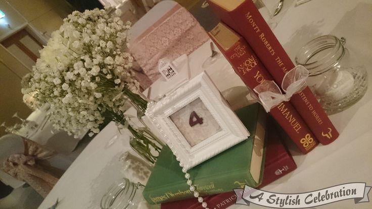 Fresh babies breath, pearls, books and photo frame table numbers make a beautiful centrepiece for a vintage wedding. #vinage #wedding #love #freshflowers #centrepiece #bride #unusual #astylishcelebration www.astylishcelebration.com.au