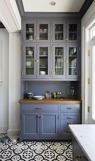 An old, dark kitchen get's a bright new makeover with beautiful blue and white tile floors, spacious cabinet storage and lots of natural light.