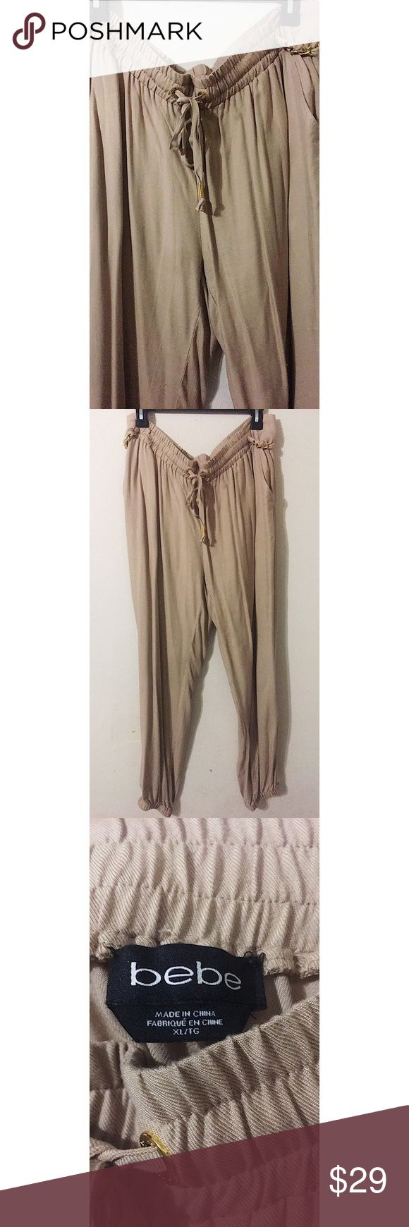 💋 Bebe cuffed jogger pants 💝 Tan cuffed jogger pants with gold chain details on sides. Bebe gold detail on back pocket. Drawstring elastic waistband for comfort and adjustment. Functional front pockets. 100% Rayon. I love the soft material. High quality material with a little wear as shown in picture. Last photo does not reflect true color. True color shown in first photos. 💕 bebe Pants Track Pants & Joggers