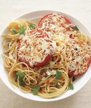 Basil Spaghetti With Cheesy Broiled Tomatoes recipe: Instead of the usual tomato sauce, serve spaghetti with fresh tomatoes covered in melted mozzarella and Parmesan.